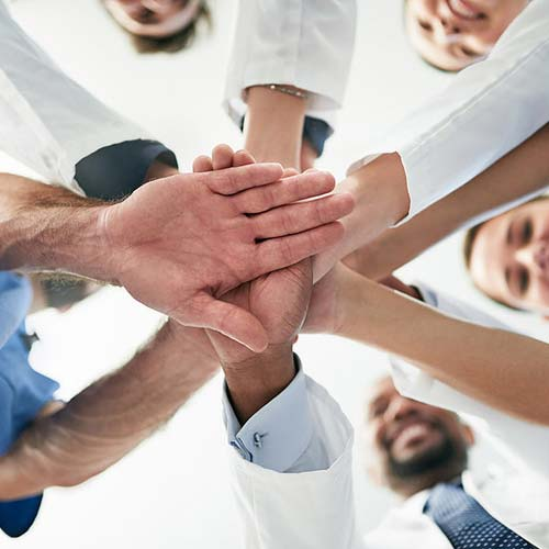 All doctors putting hands together to show teamwork.